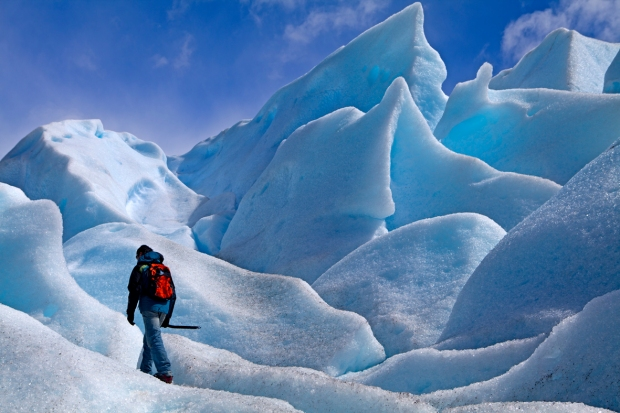 Walker among ice formations on Moreno Glacier