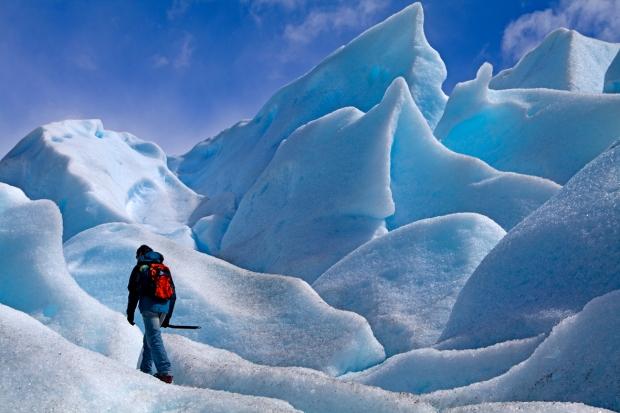 Walker among ice formations on Moreno Glacier