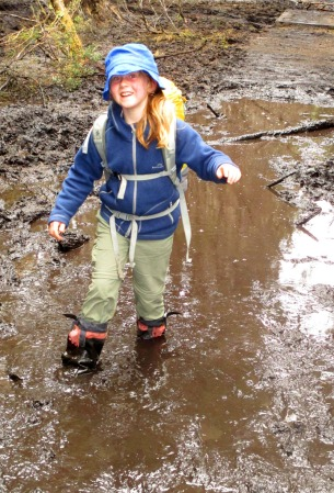 Kiri crossing through mud near Frog Flats on the Overland Track