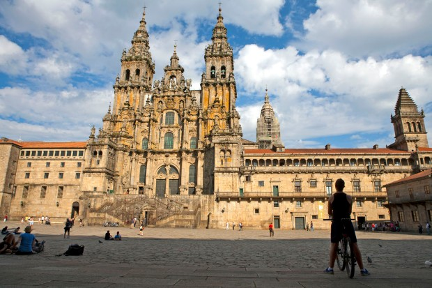 A cyclist contemplates journey's end by the Santiago cathedral.